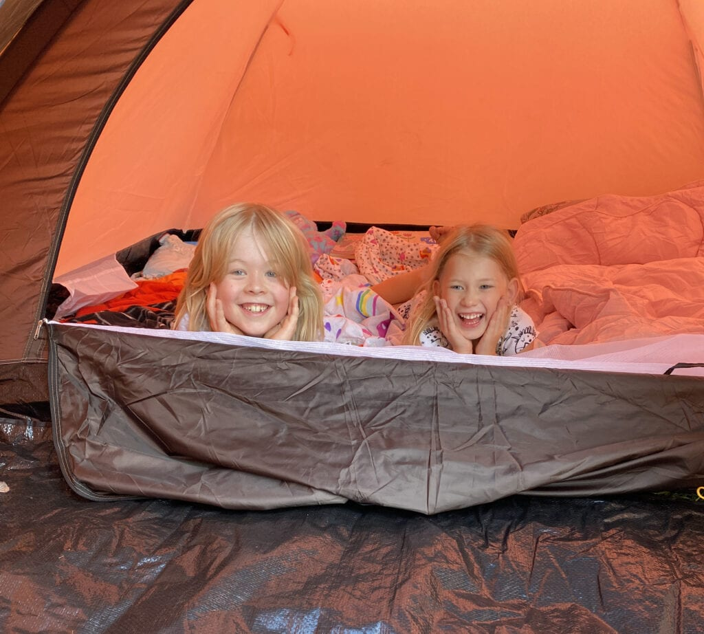 Logan and Aria laughing peering out of an orange tent in the garden