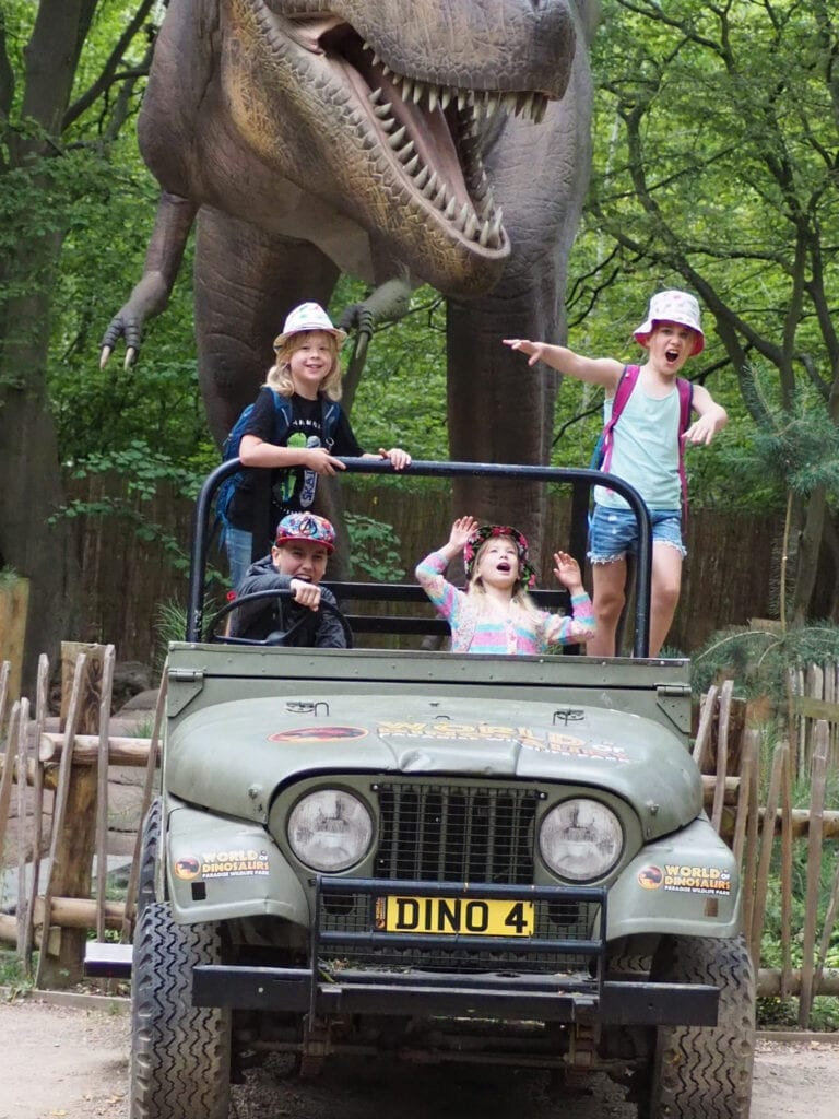 4 children in a car (prop) pretending to be chased by an animatronic dinosaur in the background making silly faces