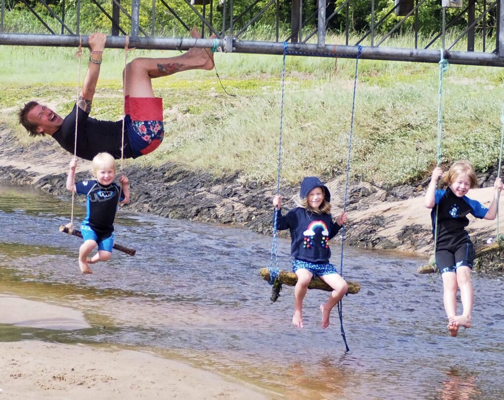 Three children on rope swings hanging off a bridge with their Dad photo bombing behind hanging off of the bridge