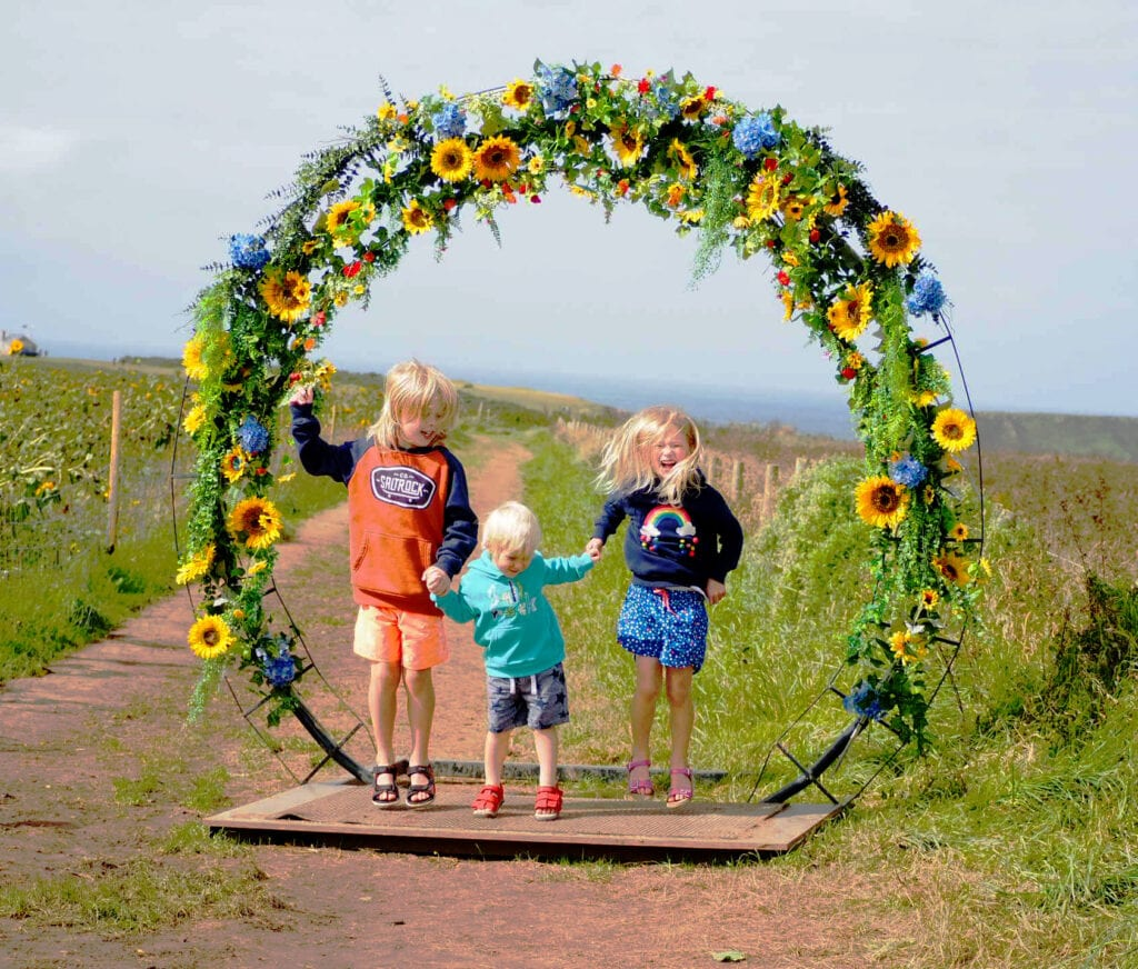 Logan, Aria and Bo jumping with a hope of sunflowers in the background and the sea in the horizon behind them