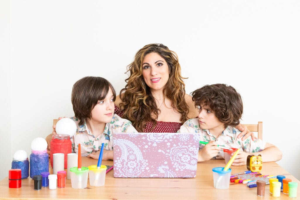 Picture of Vicki Broadbent - Honest Mum with a lap top and her two sons surrounded by toys.