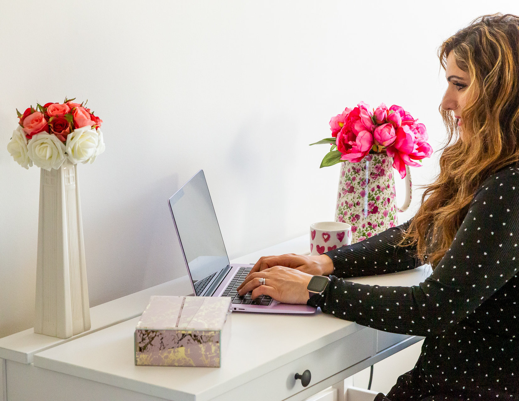 Picture of Vicki Broadbent sat at a laptop on a white desk with two vases of flowers