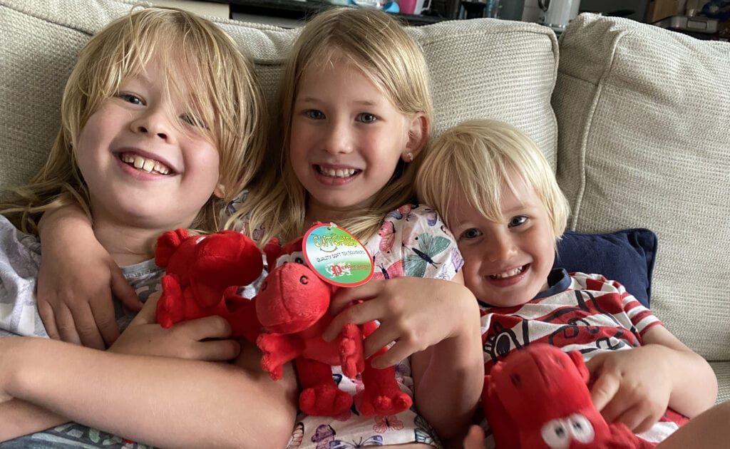 Logan, Aria and Bo cuddled on the sofa with red welsh red dragon teddies