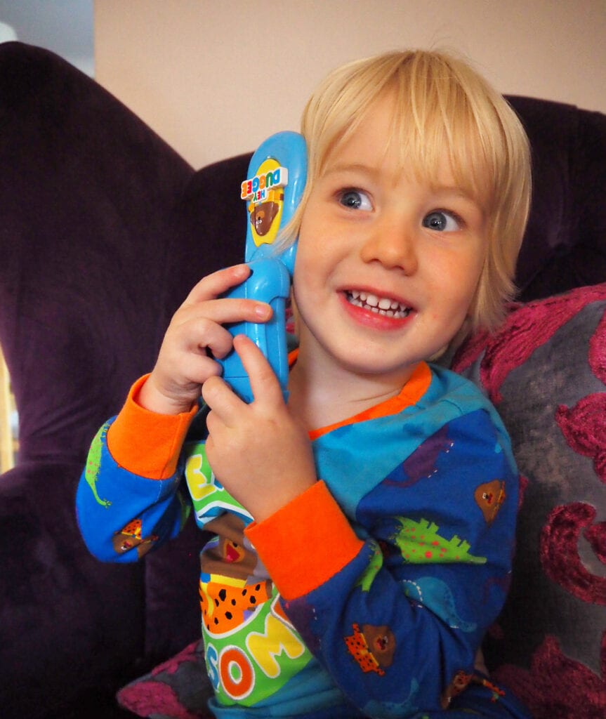 Bo in Hey Duggee pjs smiling and holding Hey Duggee flip phone to his ear