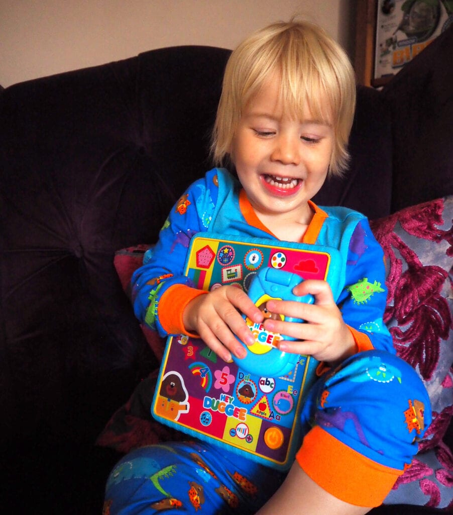 Bo smiling and delighted with his Hey Duggee toys