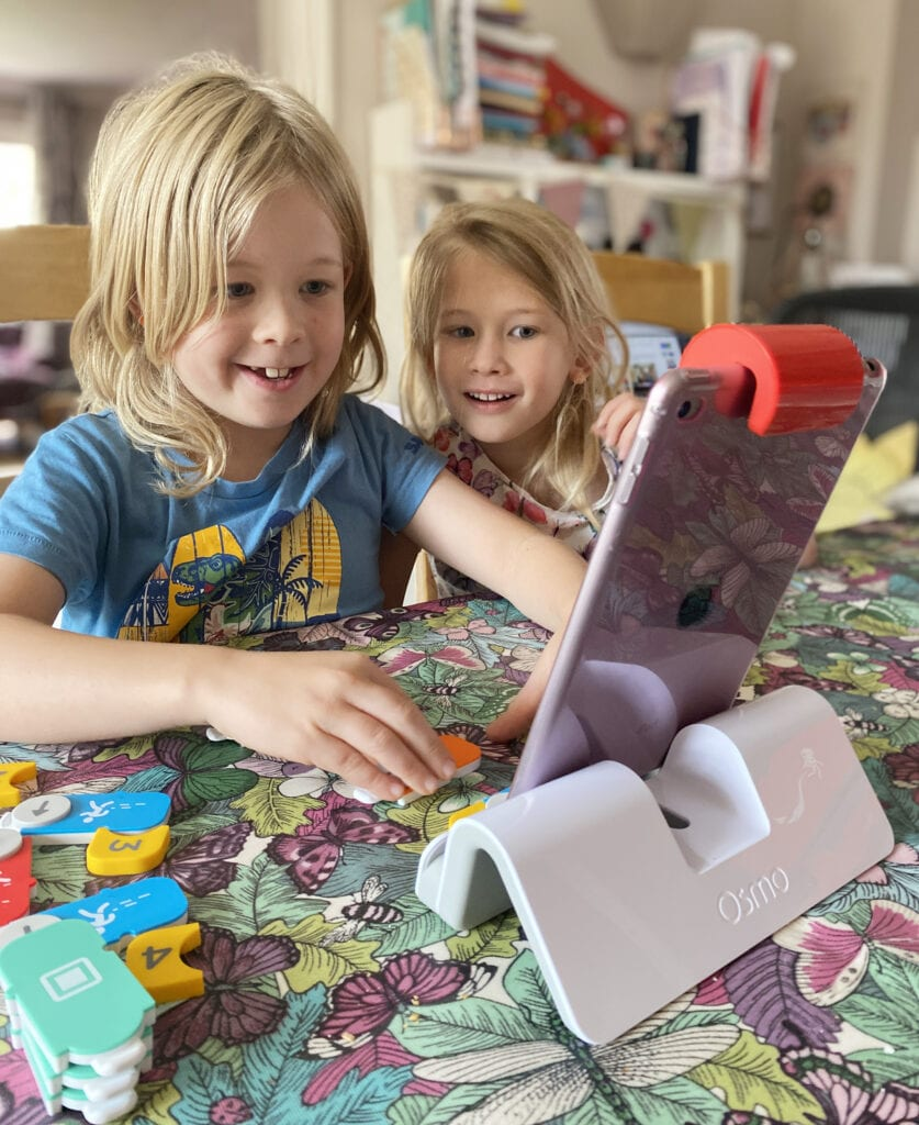 Picture of two children smiling and playing the Osmo on an iPad