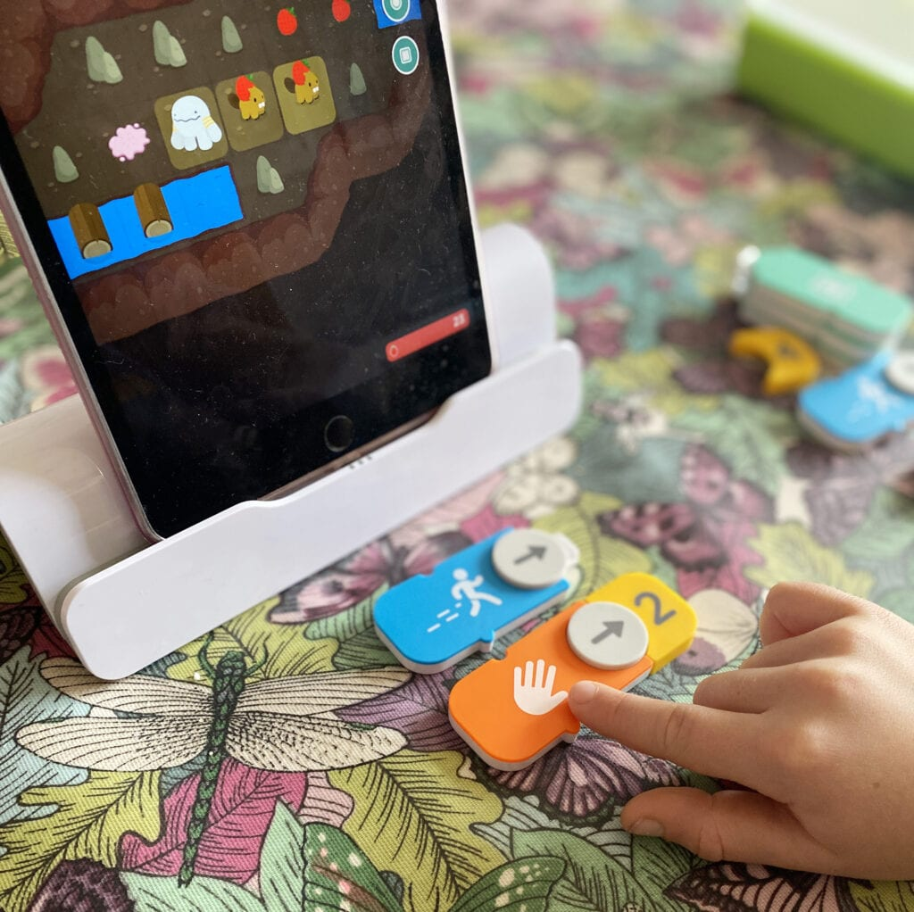 Picture of ipad with Osmo kit attached to it and a child connecting coding bricks together