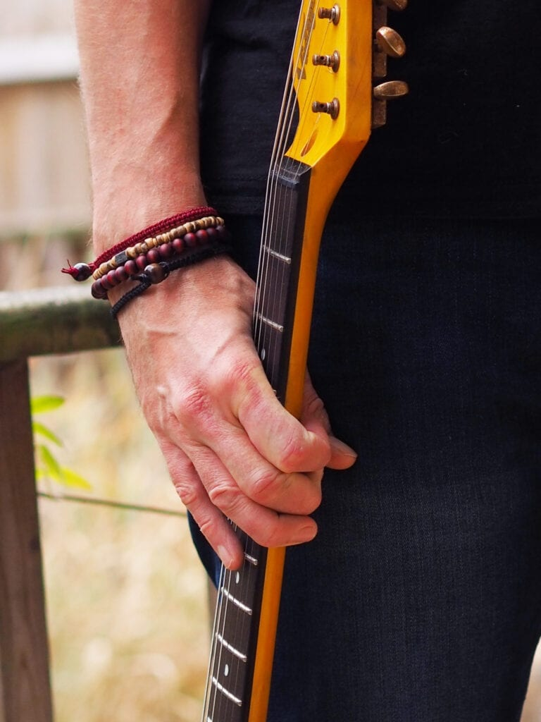 Trend Him stacking bracelet on a man's wrist. Man is also holding the neck of a guitar