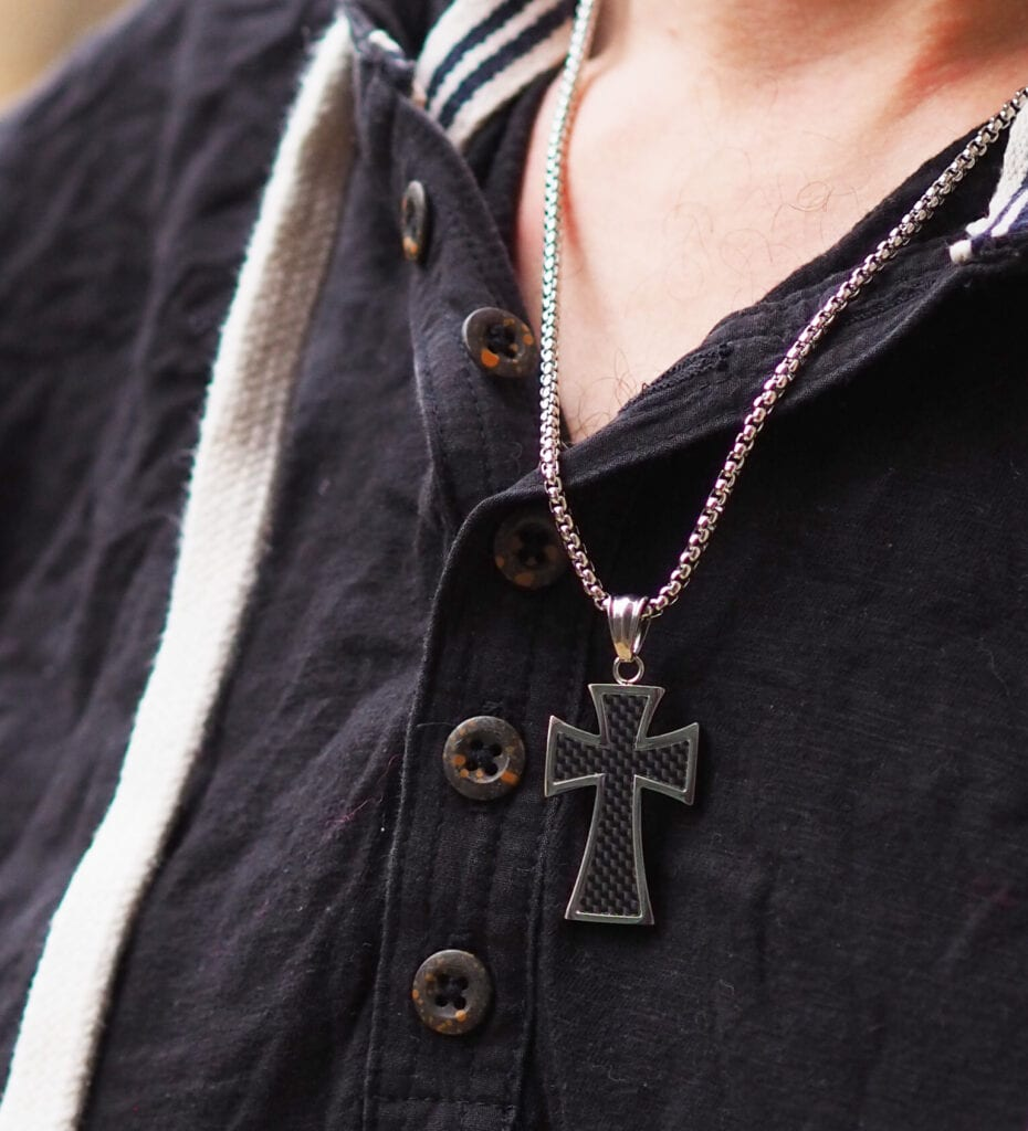 Trend Him Byzantine cross necklace. Close up on necklace on a man with a black top.