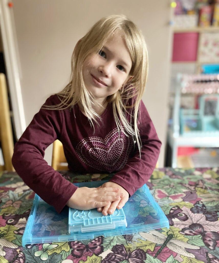 Aria pressing a board onto her aquabead creation