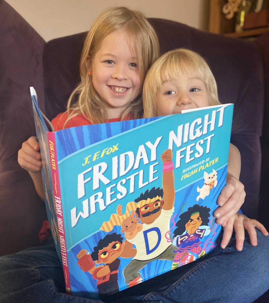 CHILDREN'S BOOK REVIEW: Friday Night Wrestlefest by J.F. Fox - two boys sat on a chair grinning and reading the book